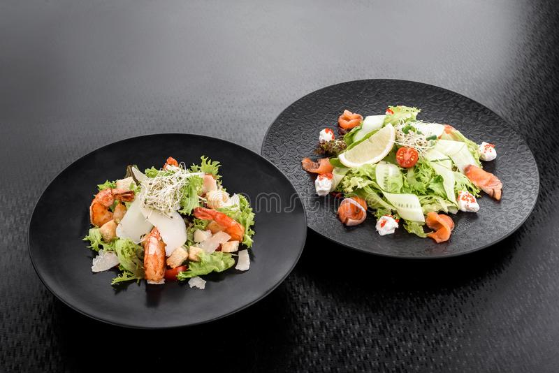 Caesar sałatka z garnelami i sałatka z łososiem, kremowym serem i ogórkiem na czarnych talerzach na ciemnym tle, obrazy stock