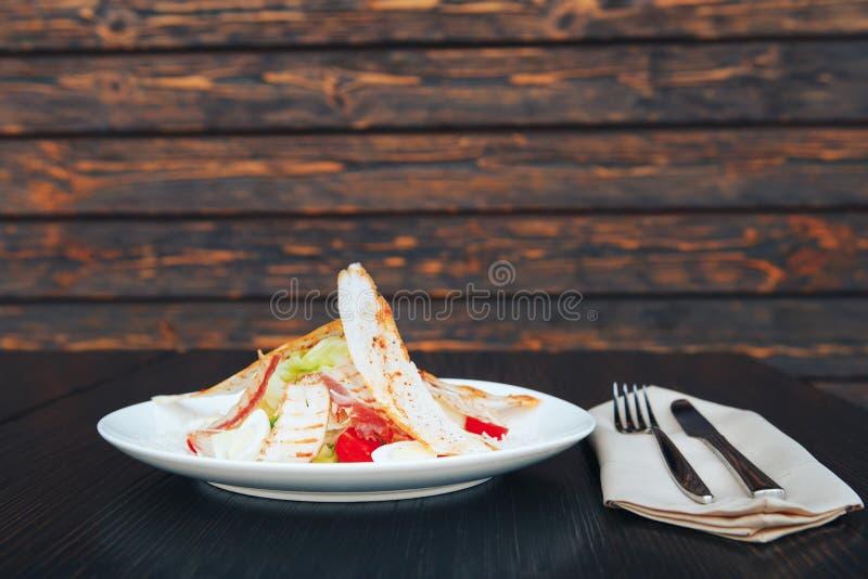 Caesar sałatka z kurczakiem i zielenie na drewnianym stole Talerz z kurczak sałatką na stole zdjęcia stock
