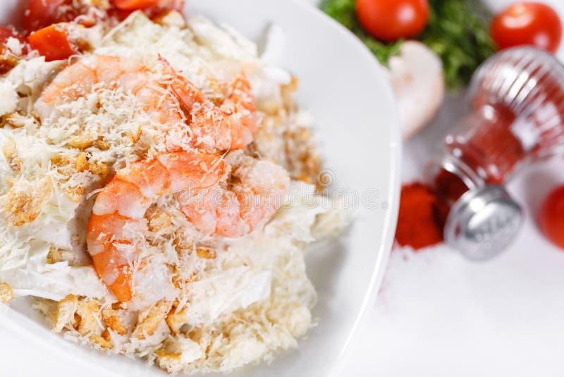 Caesar Salad avec les crevettes royales Comporte la feuille et les croûtons de salade 'Iceberg' préparés avec le parmesan Lumière photos stock