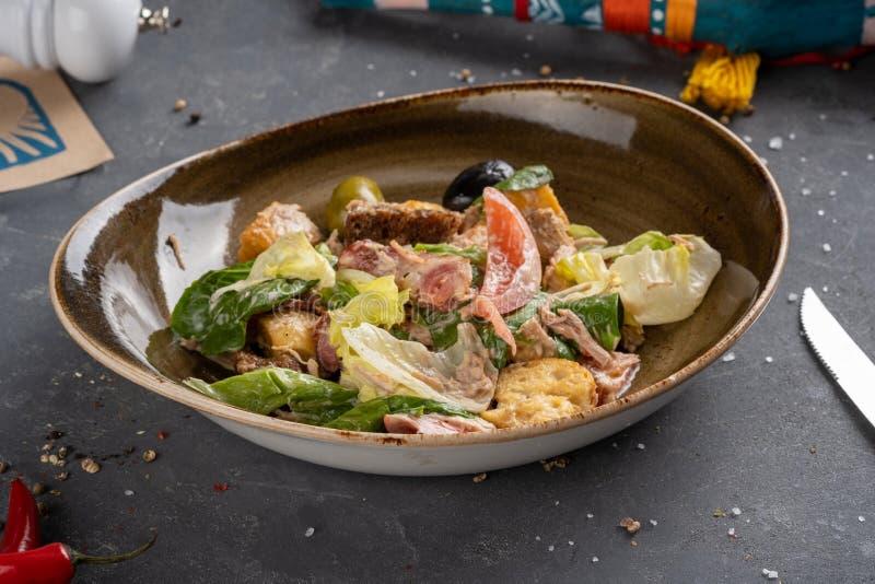 Caesar Salad Bacon förläggas i en maträtt på en tabell arkivfoton