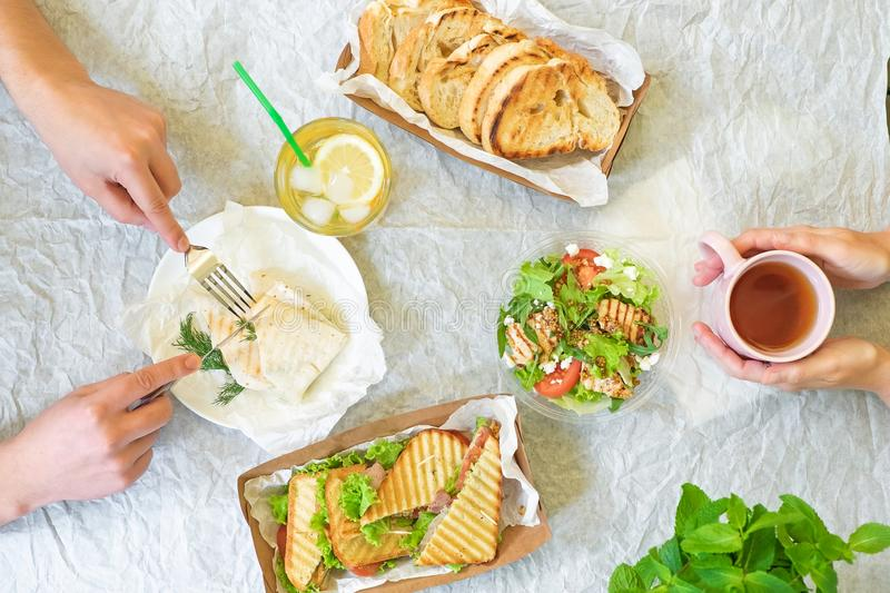 Caesar salad, bruschetta, ham and tomato sandwiches table with hands, top view from above stock photos