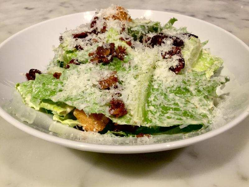 Caesar Salad. Classic. Fresh Salad dish. Marble table. A Caesar salad is a green salad of romaine lettuce and croutons dressed with lemon juice, olive oil, egg stock photo