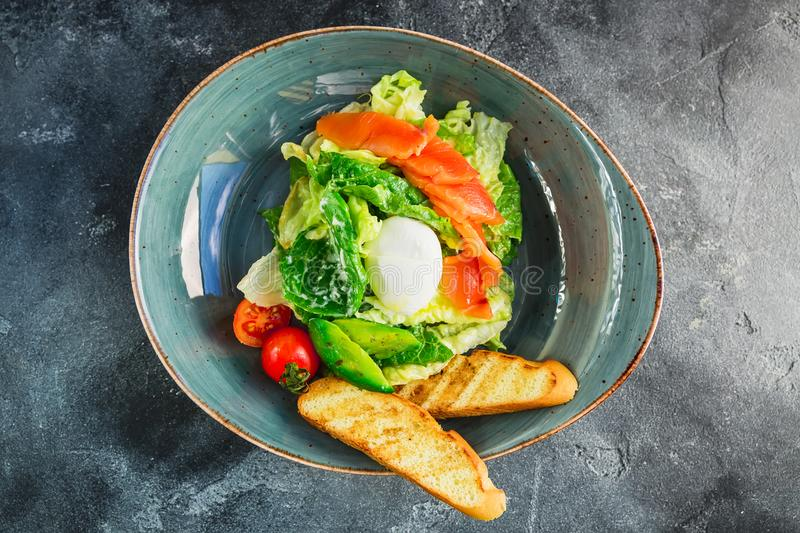 Caesar salad with eggs, salmon, avocado, cherry tomatoes and grilled toast, close up view. Tasty food in cafe stock photography