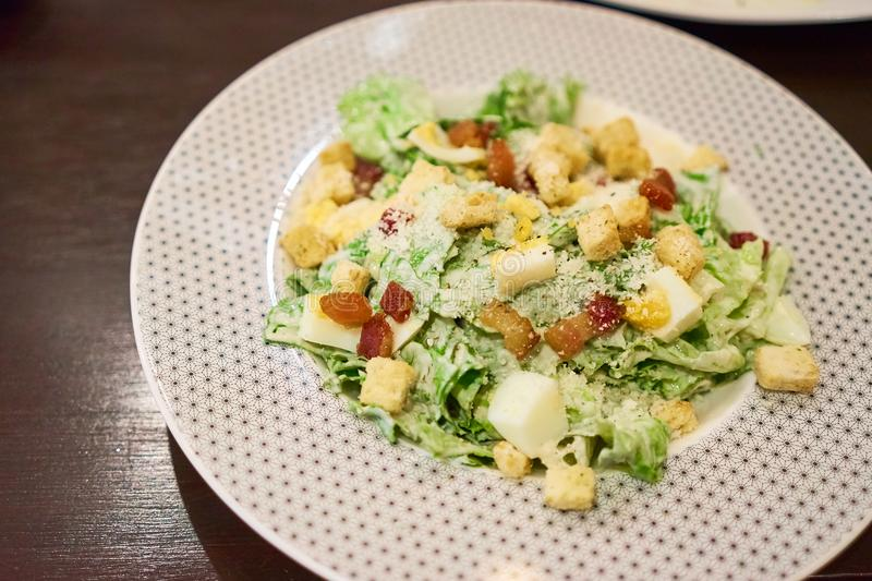 Caesar salad is a green salad of romaine lettuce, Bacon Fried and croutons in white plate. Caesar salad is a green salad of romaine lettuce, Bacon Fried and stock image