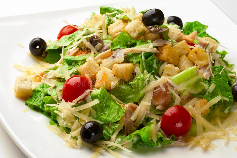 Caesar Salad. Isolated on plate with croutons cherry tomatoes and black olives royalty free stock photos