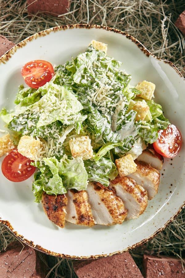 Caesar Salad met Gesneden Kippenfilet op Rustiek Hay Background stock foto