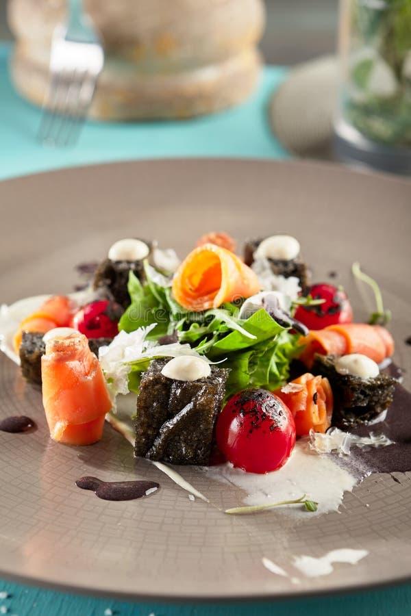 Caesar Salad noir avec les saumons fumés photo libre de droits