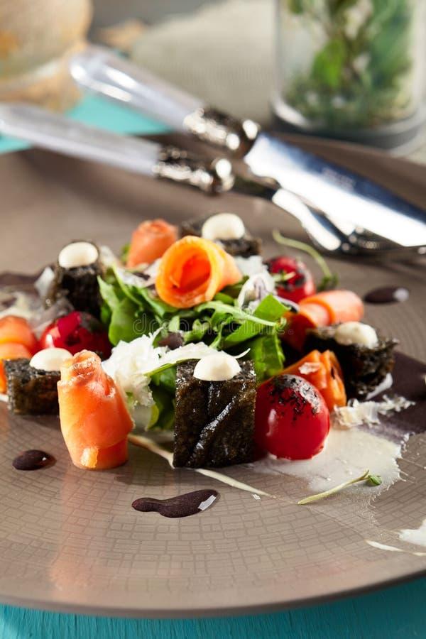 Caesar Salad noir avec les saumons fumés image libre de droits