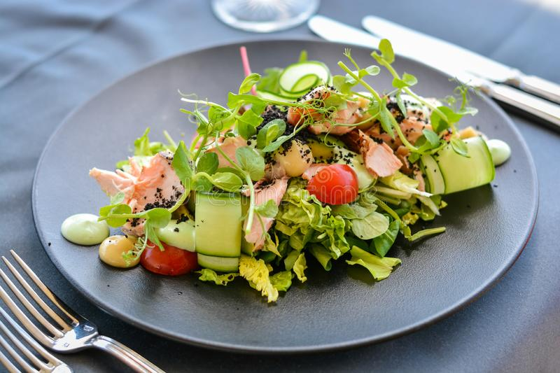 Caesar salad with salmon on black dish. In restaurant. Knives and forks on the side stock photo