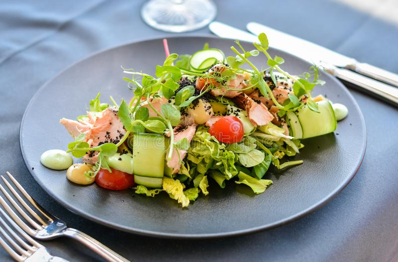 Caesar salad with salmon on black dish. In restaurant. Knives and forks on the side royalty free stock photography