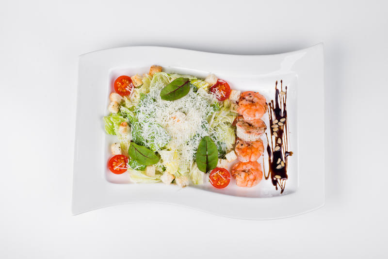 Caesar salad with tiger prawns, tomatoes and herbs on white plat royalty free stock photography