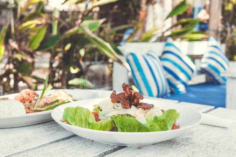 Caesar Salad on a white wooden table in the beach cafe, Bali island. royalty free stock photography