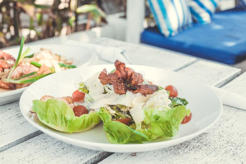 Caesar Salad on a white wooden table in the beach cafe, Bali island. Indonesia stock image