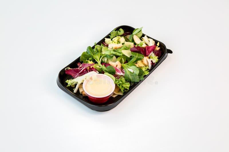 Caesar-Salat auf einem schwarzen Behälter mit weißem Hintergrund stockbilder
