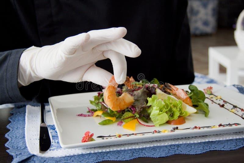Caesar-Salat mit Garnelen auf einer Platte und einer Hand von kitchener stockfoto