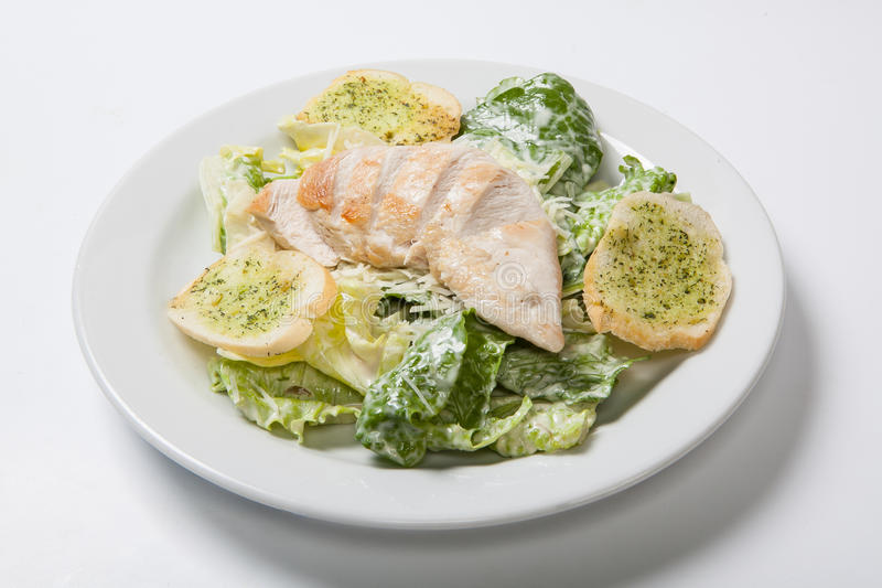 Caesar-Salat mit Huhn auf weißer Platte stockbild
