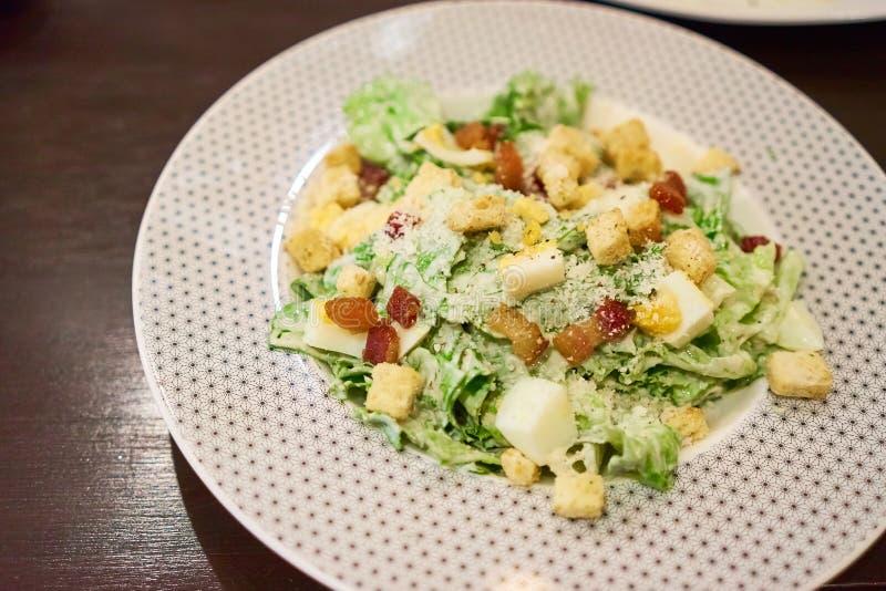 Caesar sallad är en grön sallad av bindsallat, stekt bacon och krutonger i den vita plattan fotografering för bildbyråer