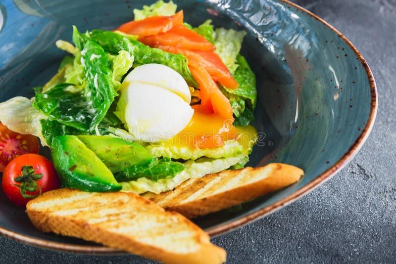 Caesar sallad med ägget, laxen, avokadot, körsbärsröda tomater och grillat bröd, övre sikt för slut arkivfoto