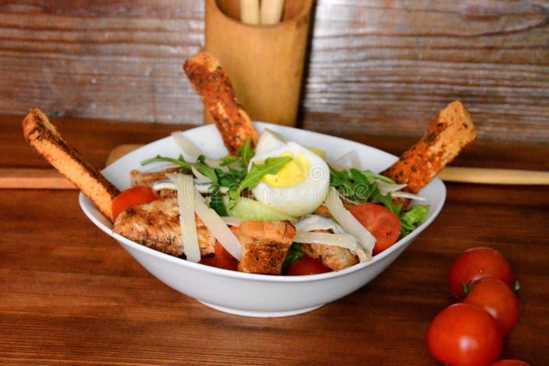 Caesar sallad med den vita krutongen, körsbärsröda tomater, höna och ägg som klär på träbakgrundsslut upp Mat och hälsa royaltyfria bilder