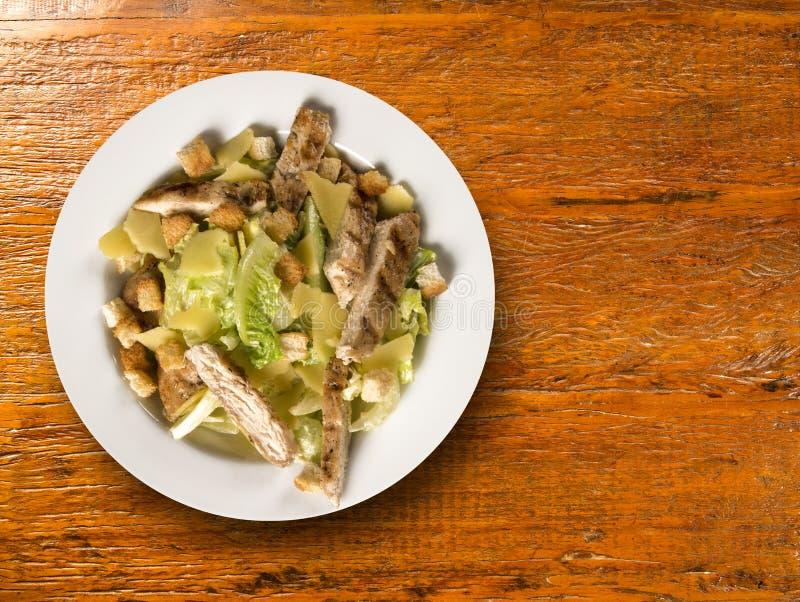 Caesar sallad med krutonger och grillad höna på trätabellen arkivfoton