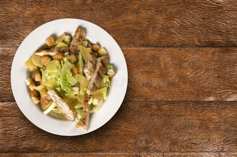 Caesar sallad med krutonger och grillad höna på trätabellen arkivfoto