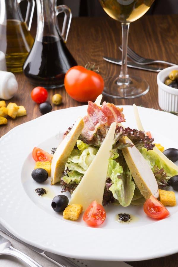 Caesar sallad med krutonger, ost och grillad höna tjänade som på en tabell arkivbilder