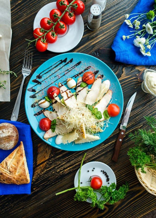 Caesar sallad med krutonger, vaktelägg, körsbärsröda tomater och gril arkivfoto