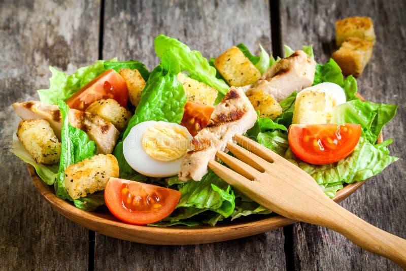 Caesar sallad med krutonger, vaktelägg, körsbärsröda tomater och grillad höna i träplatta royaltyfri foto
