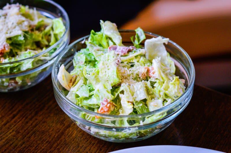 Caesarsalade in een glaskom op lijst wordt geplaatst die stock foto