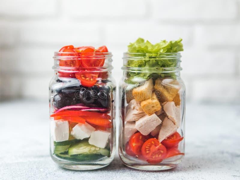 Caesarsalade en Griekse Salade in de kruik van de glasmetselaar stock foto's