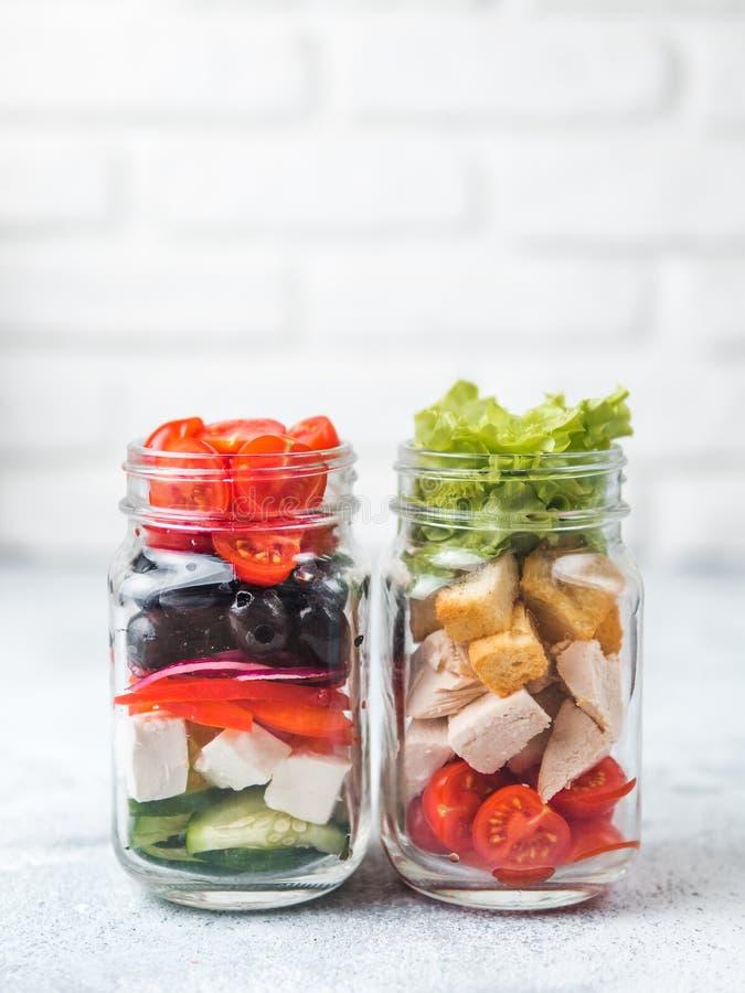 Caesarsalade en Griekse Salade in de kruik van de glasmetselaar stock fotografie