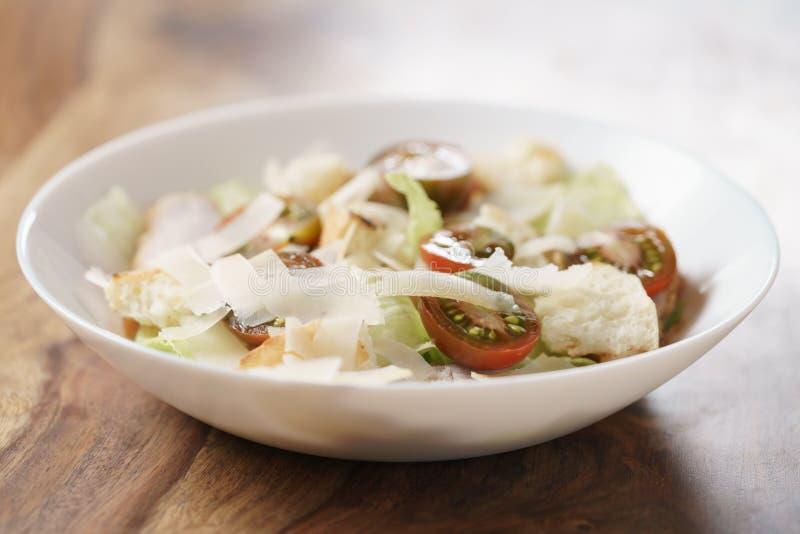 Caesarsalade met de tomaten van kersenkumato op houten lijst stock foto