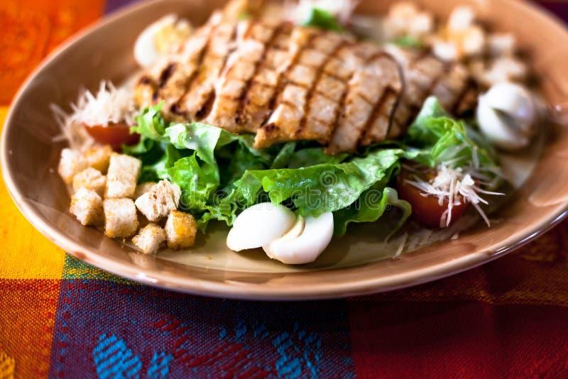 Caesarsalade met geroosterde kip op een plaat Geroosterde kippenborsten en verse salade in een plaat stock fotografie