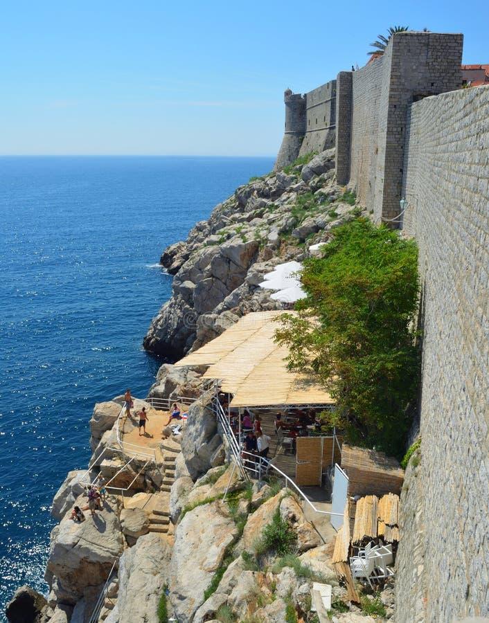 Café auf den Felsen, die außerhalb Dubrovnik-Stadtmauern anhaften lizenzfreies stockfoto