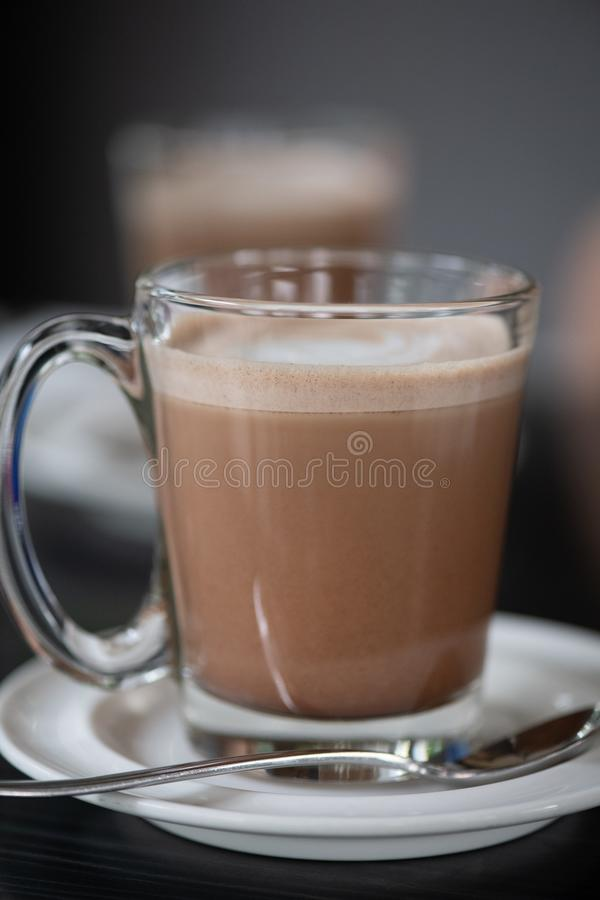 Café-lattes im Glas auf keramischer Platte stockbild