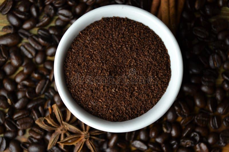 Cafè moulu dans la tasse blanche avec des grains de café à l'arrière-plan image libre de droits