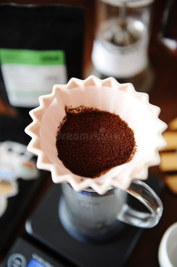 Cafè moulu dans le dispositif d'écoulement en céramique rose d'origami avec le filtre de papier Brassage alternatif de café Broye images libres de droits