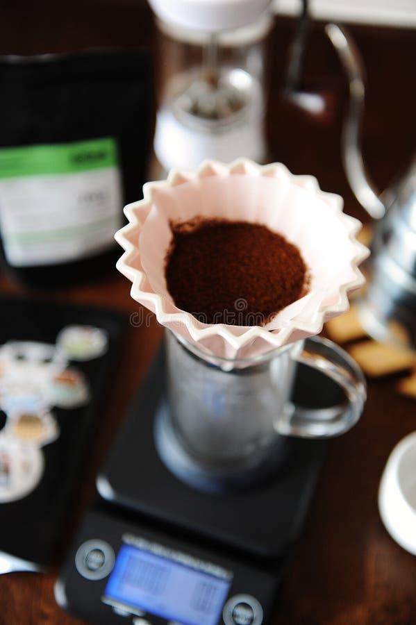 Cafè moulu dans le dispositif d'écoulement en céramique rose d'origami avec le filtre de papier Brassage alternatif de café Broye photo stock