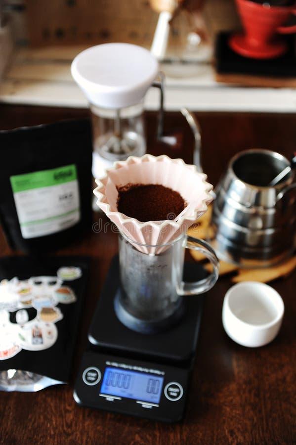 Cafè moulu dans le dispositif d'écoulement en céramique rose d'origami avec le filtre de papier Brassage alternatif de café Broye photographie stock libre de droits