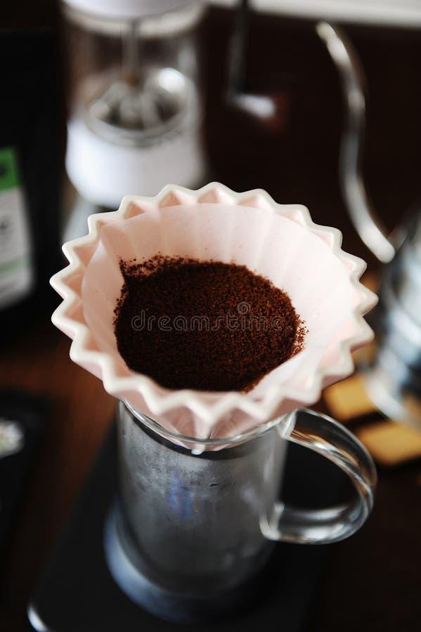 Cafè moulu dans le dispositif d'écoulement en céramique rose d'origami avec la fin de papier de filtre  Brassage manuel de main d photos libres de droits