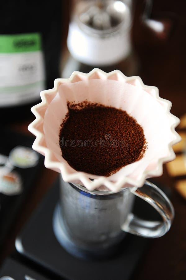 Cafè moulu dans le dispositif d'écoulement en céramique rose d'origami avec la fin de papier de filtre  Brassage manuel de main d photographie stock libre de droits