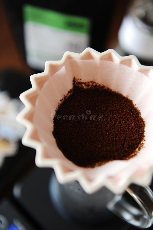 Cafè moulu dans le dispositif d'écoulement en céramique rose d'origami avec la fin de papier de filtre  Brassage manuel de main d photo libre de droits