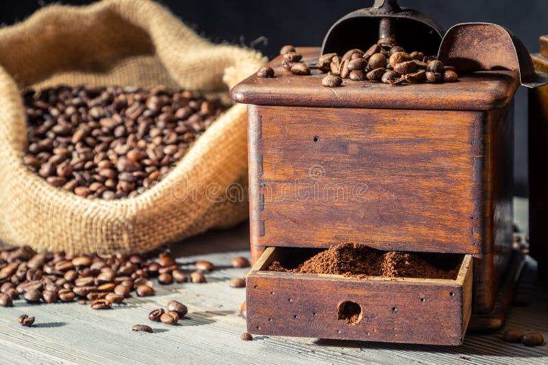 Cafè moulu dans le grider de cru et haricots dans le sac photographie stock libre de droits
