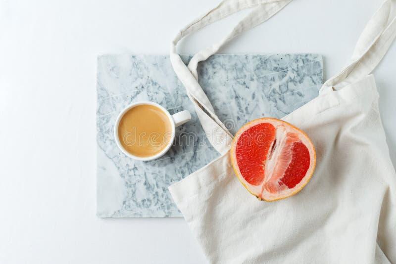 Café étendu plat avec le sac de tissu de métier d'eco et pamplemousse du plat de marbre et du fond blanc Concept minimal de hippi photo stock