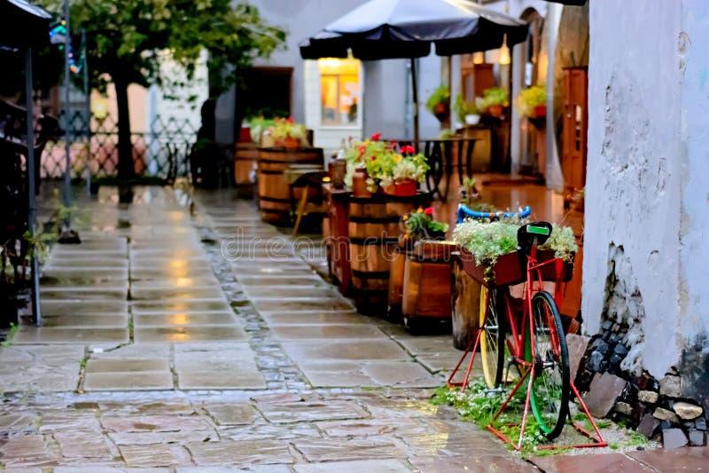 Café abandonado quieto e acolhedor da rua na chuva do outono Bicicleta velha decorada com flores imagem de stock royalty free