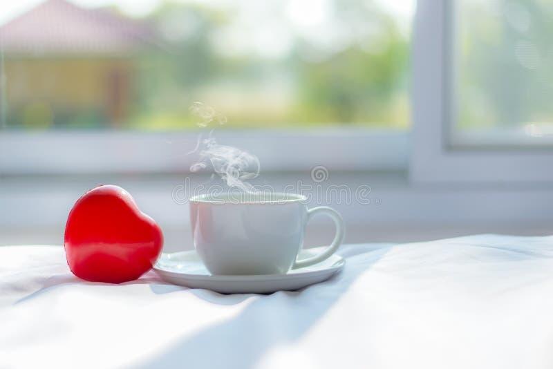 Café acogedor fresco de la mañana en la cama blanca con forma roja del corazón cerca de la ventana en el día soleado, fondo verde foto de archivo