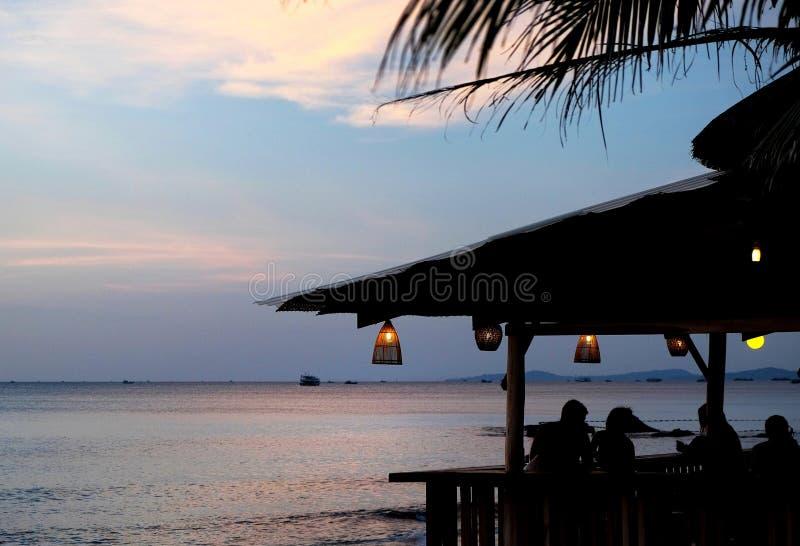 Café acolhedor com as lâmpadas de bambu na praia no por do sol bonito foto de stock