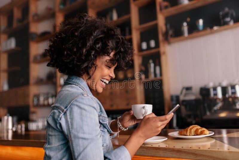 Café africain de femme utilisant le téléphone portable et le sourire photographie stock libre de droits