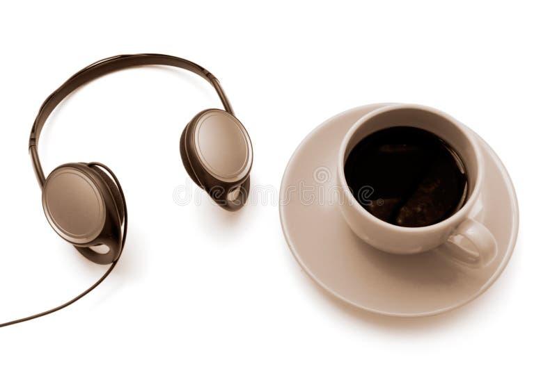 Café aislado del ofr de la taza con los auriculares foto de archivo