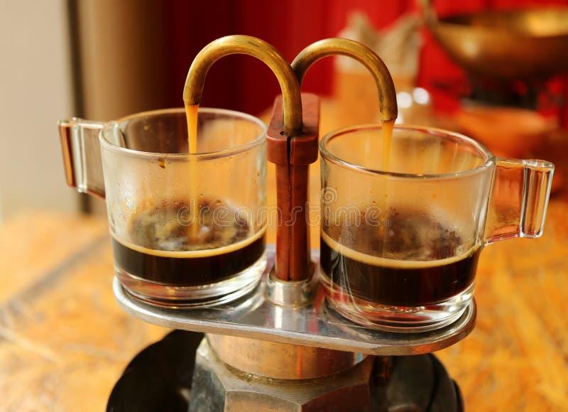 Café aromatique s'écoulant goutte à goutte du mini rétro pot de brassage dans une paire de tasses en verre de tasse à café photo stock